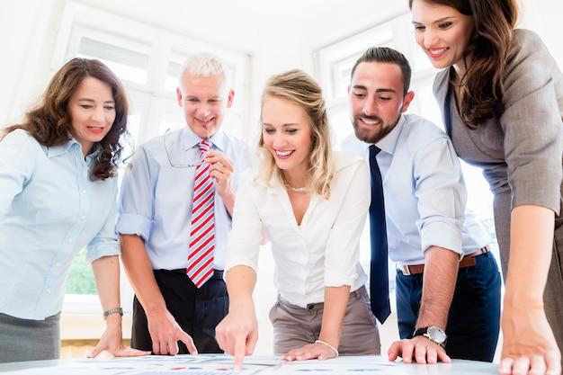 Geschäftsteam im strategietreffen, das zahlen und daten bespricht