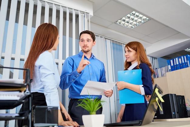 Geschäftsteam in einem büro, das mit dokumenten sich verständigt