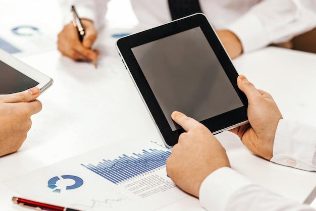 Geschäftsteam mit digitalem tablet und smartphone, das mit fi . arbeitet