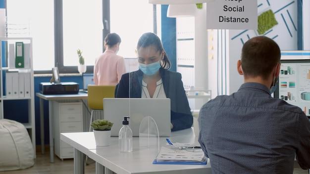 Geschäftsteam mit gesichtsmasken, das im firmenbüro arbeitet und vorkehrungen trifft, um sicherheitsmaßnahmen aufrechtzuerhalten, um eine infektion mit dem coronavirus zu vermeiden. kollegen respektieren die soziale distanzierung während der quarantäne von covid19