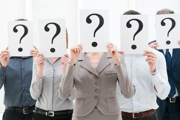 Geschäftsteam versteckt ihre gesichter hinter fragezeichenschildern im büro