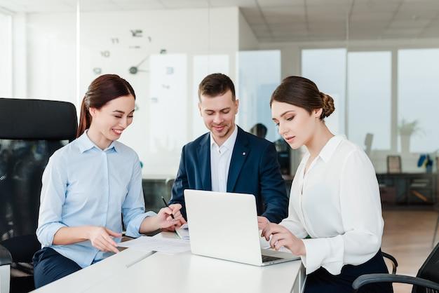 Geschäftsteam von den leuten, die im büro an einem laptop arbeiten