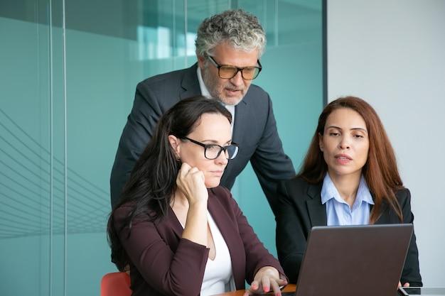Geschäftsteam von drei, das präsentation am computer beobachtet, anzeige betrachtet, details bespricht