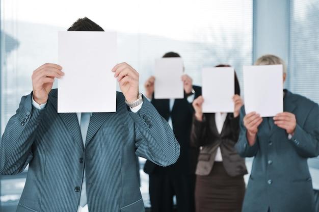 Geschäftsteam von vier leerem papier halten