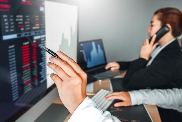 Geschäftsteamabkommen investitionsbörse, die aktienhändler des diagrammbörsenhandels bespricht