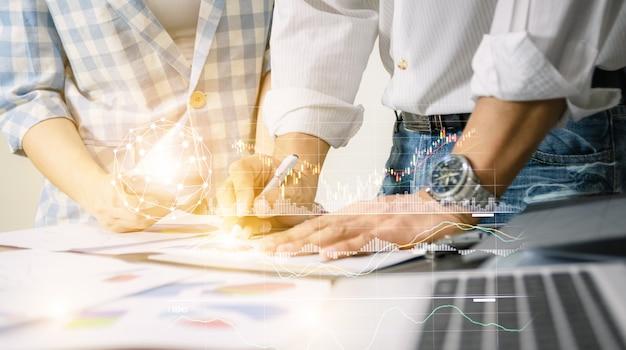 Geschäftsteamarbeit, die diagrammnetz-technologiewelt das schreibtischnotizbuch auf hölzerner tabellendarstellung analysiert.