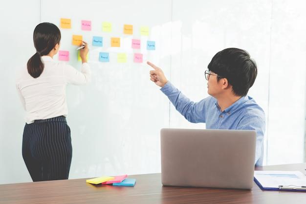 Geschäftsteamarbeit in besprechung und haftnotiz auf spiegelplatte, die mit team im büroraum für das sammeln eines ideen-brainstorming-plans besprochen wird.