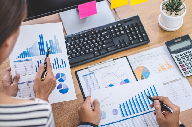 Geschäftsteambesprechung, die mit neuem startprojekt, diskussion und analysedaten die diagramme und diagramme, computer unter verwendung arbeitet