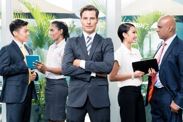 Geschäftsteambesprechung mit dem mann in der front, die kamera betrachtet