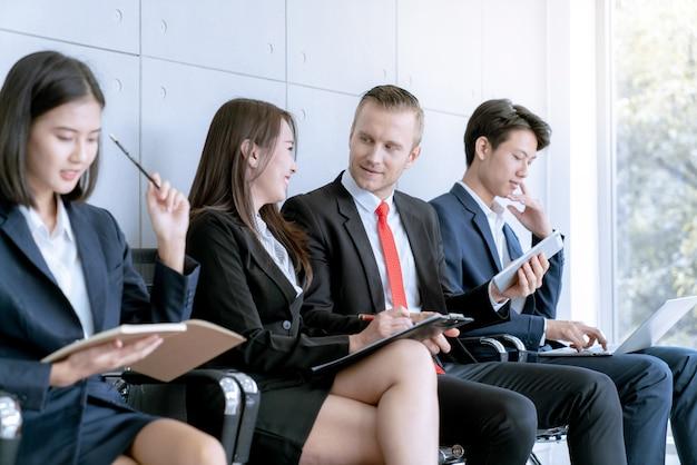 Geschäftsteamwork, das arbeit beim warten auf anwesendes projekt zum kunden bespricht