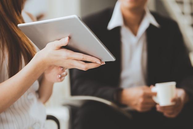 Geschäftstechnologiekonzeptgeschäftsfrauen, die das arbeiten an tablette halten