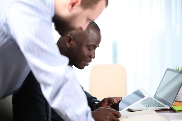 Geschäftstreffen. draufsicht auf das brainstorming des geschäftsteams beim gemeinsamen sitzen am bürotisch