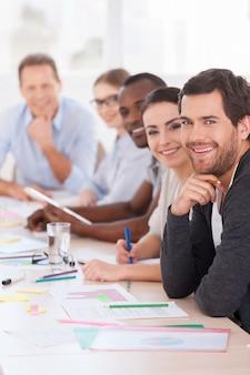 Geschäftstreffen. gruppe von geschäftsleuten in freizeitkleidung, die in einer reihe am tisch sitzen und in die kamera lächeln