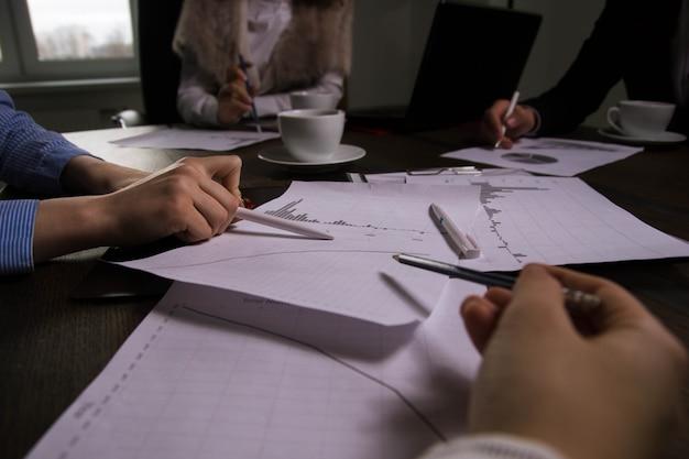 Geschäftstreffen in der bürodiskussion von finanzdiagrammen und grafiken während der kaffeedraufsicht