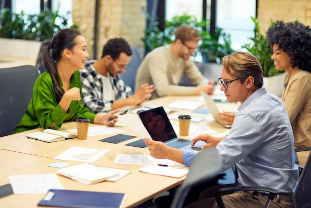 Geschäftstreffen mit gemischtrassigen menschen, die im modernen coworking space am schreibtisch sitzen