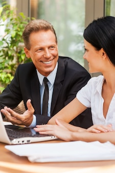 Geschäftstreffen. zwei geschäftsleute in abendgarderobe diskutieren etwas und lächeln, während beide draußen am tisch sitzen
