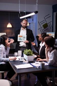 Geschäftsunternehmer, der unternehmensstatistiken mit tablet für die finanzdarstellung präsentiert
