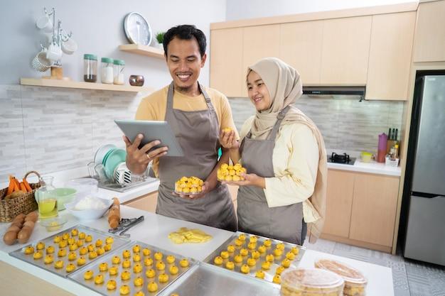 Geschäftsverkäufer des muslimischen paares, das zusammen zu hause lebensmittel bestellt. nastar ananaskuchen