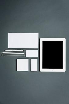 Geschäftsvorlage mit karten, papieren, tablette. grauer raum.