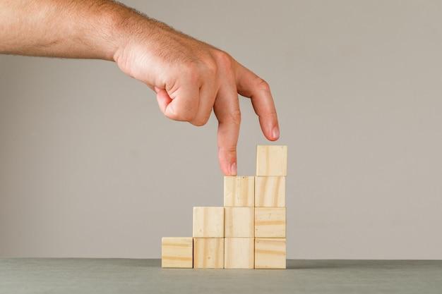 Geschäftswachstumskonzept auf grauer und weißer wandseitenansicht. mann, der finger auf stufentreppe legt.