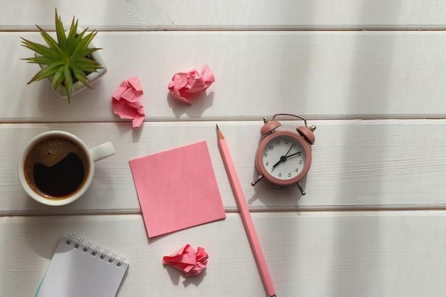 Geschäftswohnung lag mit haftnotizen, zerknittertem papier, wecker, tasse kaffee und bleistift auf holztisch.