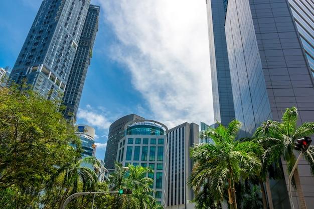 Geschäftszentrum von singapur an einem sonnigen tag. blauer himmel und wolkenkratzer. grüne bäume und ampeln an der straßenkreuzung