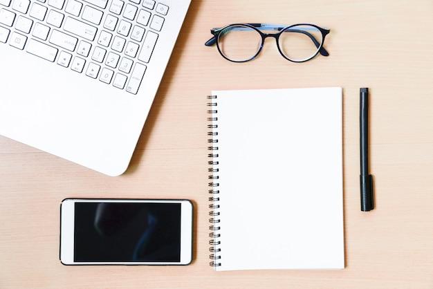 Geschäftszubehör auf dem desktop: notizbuch, tagebuch, füllfederhalter, smartphone, gläser.