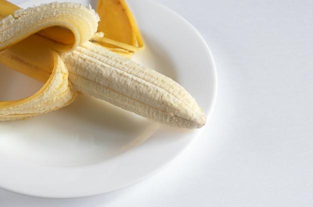 Geschälte banane auf einem teller auf weißem hintergrund