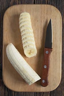 Geschälte banane auf holzschneidebrett geschnitten