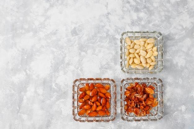 Geschälte (blanchierte) und nicht blanchierte ganze mandeln in glasschalen auf grauem beton