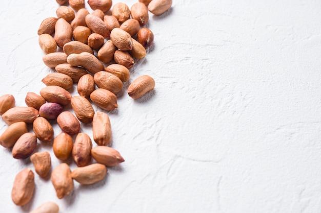 Geschälte erdnüsse auf weißem beton strukturierten hintergrund seitenansicht selektiven fokus schließen raum für text.