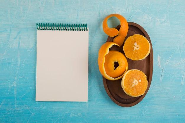 Geschälte gelbe orangen in einer holzplatte mit einem notizbuch beiseite