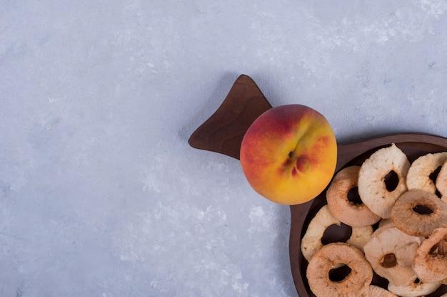 Geschälte, geschnittene und trockene äpfel mit einem pfirsich auf einer holzplatte in der ecke