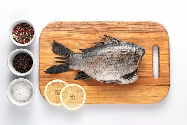 Geschälte karpfen auf einem schneidebrett mit zitronenscheiben und gewürzen, kochfertig. gesundes und diätetisches essen.
