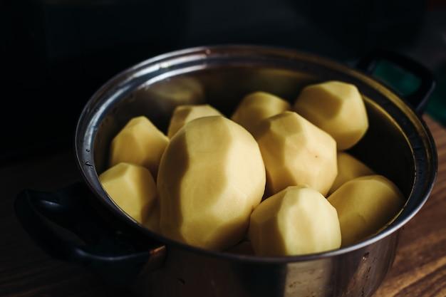 Geschälte kartoffeln in einem silbernen topf. kartoffeln zum kochen reinigen. gerichte mit geschälten kartoffeln auf dunklem hintergrund. wassertropfen