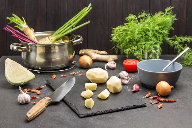 Geschälte kartoffeln und messer auf schneidebrett. petersilienwurzeln und rüben im topf. grüns und gemüse auf dem tisch. schwarzer hintergrund.