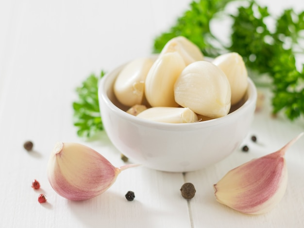 Geschälte knoblauchzehen in einer weißen schüssel mit gewürzen auf einem holztisch. gesunde natürliche gewürze. bestandteil der traditionellen medizin.
