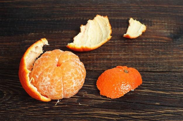 Geschälte mandarine auf altem holztisch