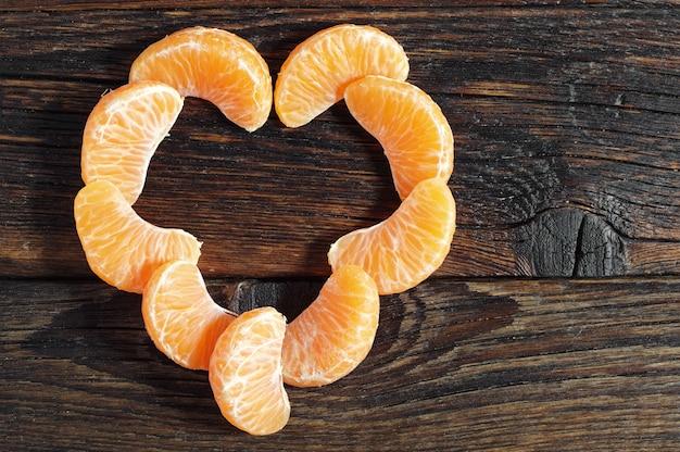 Geschälte mandarine in herzform auf rustikalem holztisch