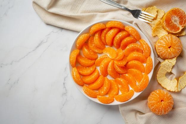 Geschälte mandarinen auf marmorhintergrund