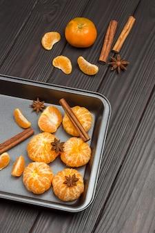Geschälte mandarinen in metallschale. sternanis, zimtstangen.