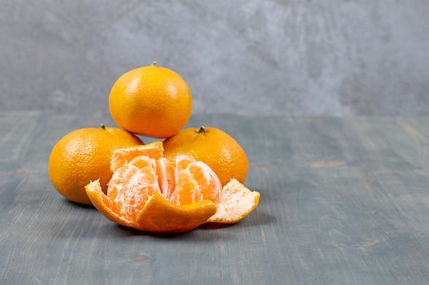 Geschälte mandarinen mit ganzen mandarinen auf marmoroberfläche