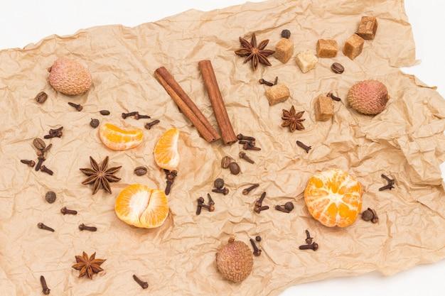 Geschälte mandarinen und gewürze. zimtstangen, sternanis, piment und kardamom, litschi und walnuss auf braunem papier. weißer hintergrund. flach liegen