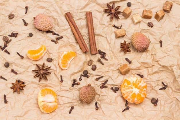 Geschälte mandarinen und gewürze. zimtstangen, sternanis, piment und kardamom, litschi und walnuss. hintergrund aus braunem papier. flach liegen