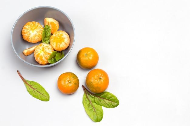 Geschälte mandarinen und mangoldblätter in grauer schüssel. ganze mandarinen und mangoldblätter auf dem tisch. grauer hintergrund. draufsicht. speicherplatz kopieren