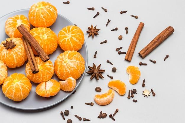 Geschälte mandarinen und zimtstangen in grauer schüssel. sternanis, zimtstangen und nelken auf dem tisch. draufsicht