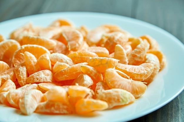 Geschälte mandarinensegmente auf teller