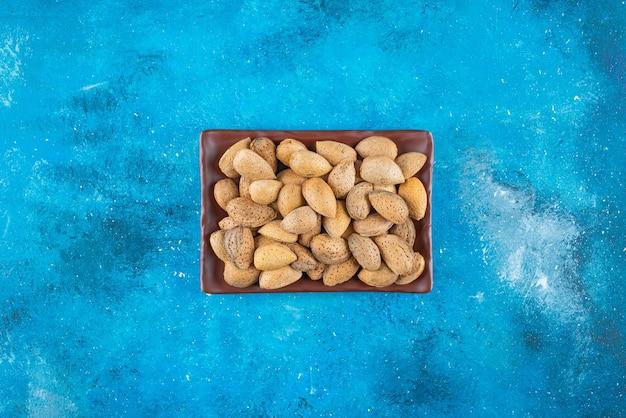Geschälte mandeln in einem teller auf dem blauen tisch.