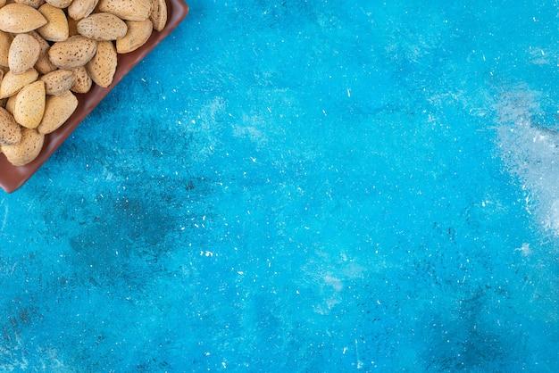 Geschälte mandeln in einem teller auf der blauen oberfläche