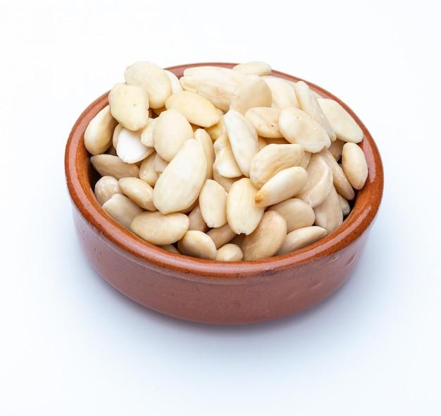 Geschälte mandeln in tonschale (sammlung verschiedener trockenfrüchte). isoliert